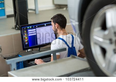 Mechanic working on car by computer in workshop