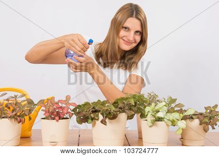 She Sprinkles Potted Plants From A Spray