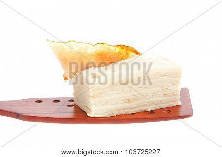 small cream cake on wooden spatula over white