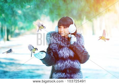 Winter woman on winter background. Woman Young girl feeding birds in the winter landscape.  Winter scene. Wonderland