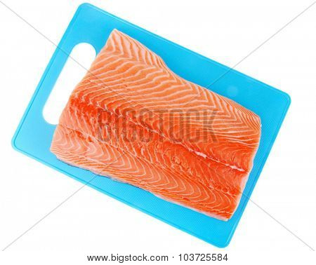 piece of salmon fillet on blue plate over white