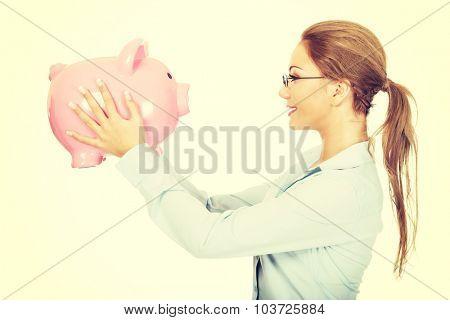 Beautiful business woman holding piggy bank.