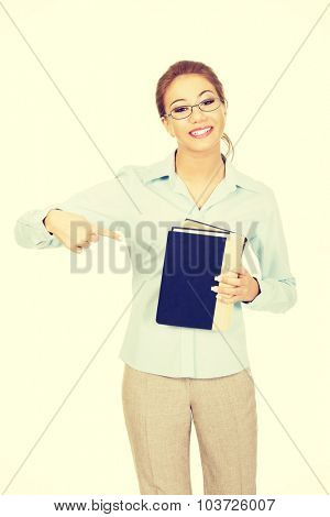 Happy business woman pointing on a book.