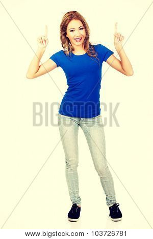 Beautiful young casual woman pointing up.