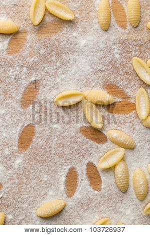top view of uncooked italian pasta with flour