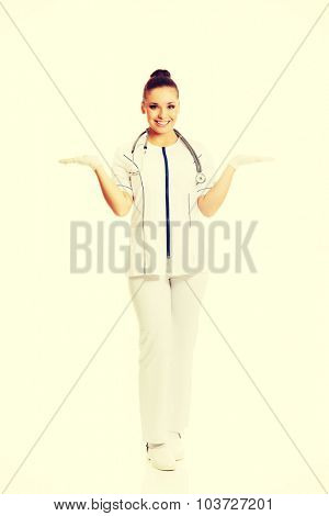 Full length female doctor presenting copyspace in both hands.