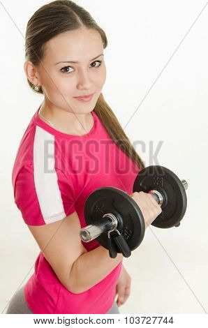 Girl Athlete Looking Up Holding A Dumbbell In Her Hand