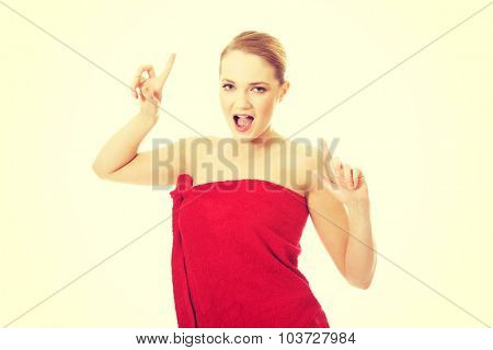 Beautiful cheerful spa woman pointing up.