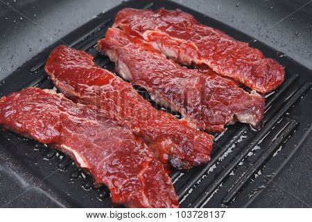 fresh raw bloody beef steaks on black grill plate isolated on white background
