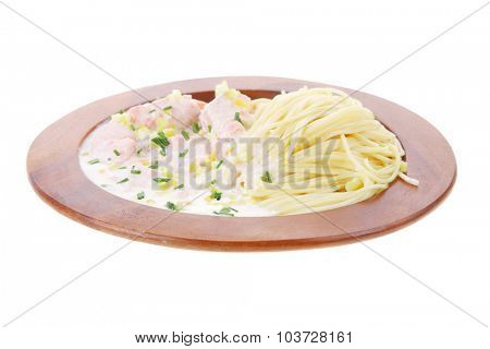 fresh rose wild salmon baked in cream cheese sauce with italian pasta on wooden plate isolated over white background