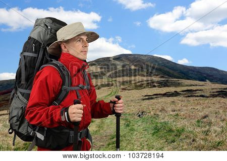 Equipped With Traveler In A Red Jacket With Hiking Poles Looks Into The Distance