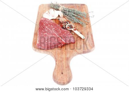 raw beef meat fillet with peppercorn and thyme ready to grill on wood board isolated over white background