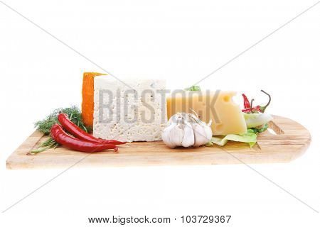 delicatessen french cheese on wooden board with hot peppers and dill isolated on white background