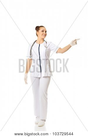 Smiling female doctor pointing to the left.