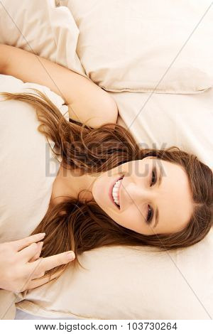 Young happy woman showing middle finger in bedroom.