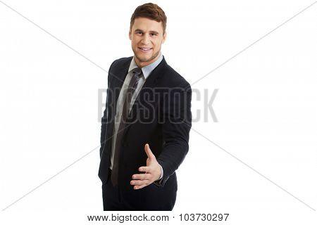 Happy handsome businessman giving a handshake.
