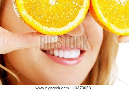 Close up woman holding oranges on eyes.