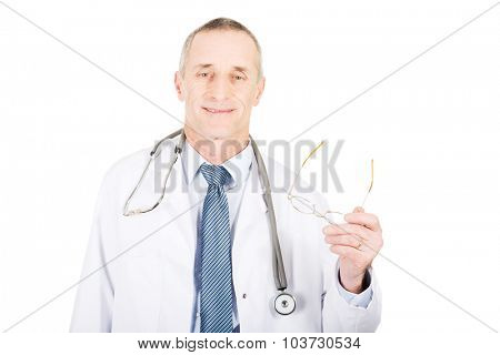 Smiling mature male doctor holding his eyewear.