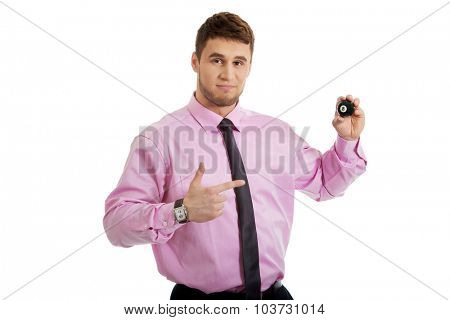 Young handsome businessman showing billiard ball.