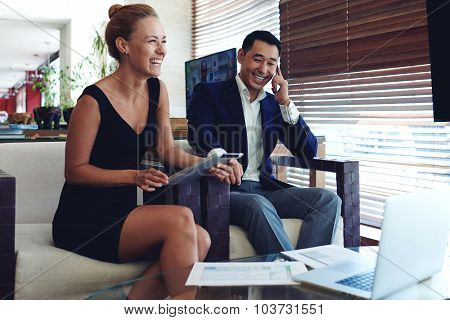 Portrait of two smiling cheerful entrepreneurs preparing for meeting