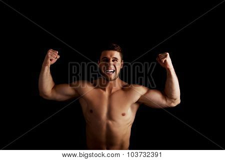 Handsome angry muscular man making fists.