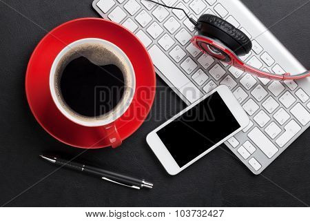 Office leather desk table with coffee cup, computer, smartphone and headphones. Top view