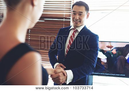 Portrait of a smiling asian men entrepreneur handshake with his female business partner