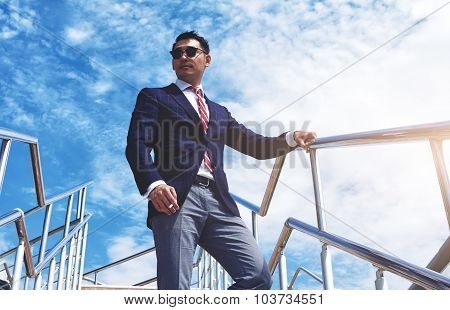 ?onfident businessman dressed in luxury suit relaxing after meeting or conference