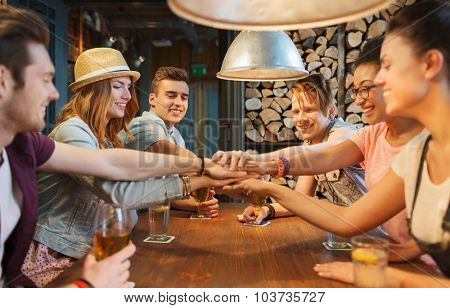 people, leisure, friendship and gesture concept - group of happy smiling friends with drinks putting hands on top of each other at bar or pub