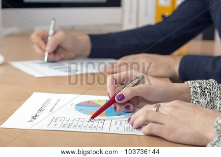 Hands of business people male and female working on printed paper charts