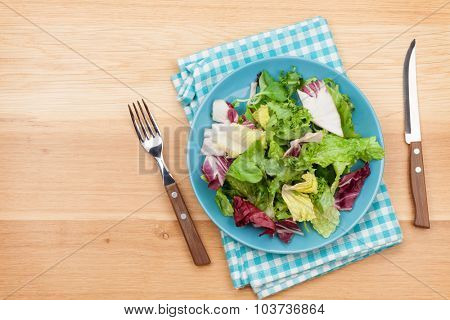 Plate with fresh salad, knife and fork. Diet food on wooden table with copy space