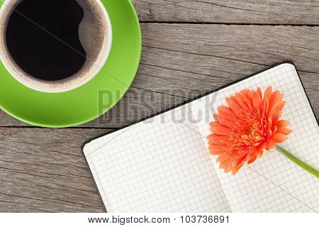 Blank notepad, coffee cup and orange gerbera flower on wooden table background