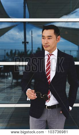 Half length portrait of a men entrepreneur dressed in elegant suit while standing near office window
