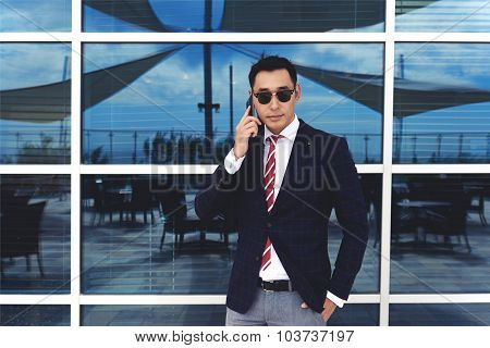 Young stylish managing director talking on his cell telephone outdoors