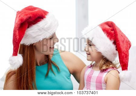 christmas, holidays, family, childhood and people concept - happy mother and little girl in santa hats at home