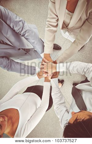 Group of colleagues making pile of hands