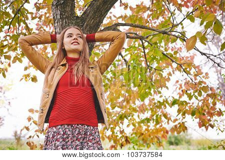 Restful girl in leather jacket and red pullover standing by tree trunk in park