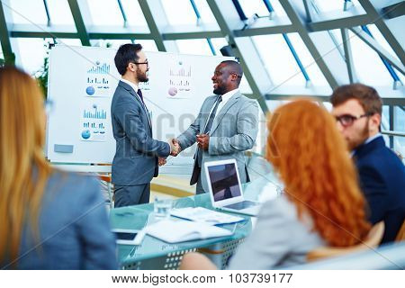 Asian and African businessmen handshaking after signing contract