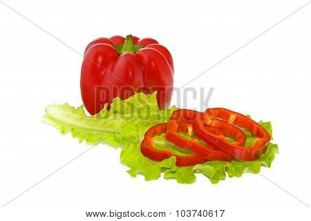 Red pepper and pepper rings lie on a salad leaf