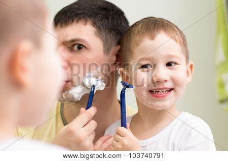 Funny man and son little child shave looking at mirror in bathroom