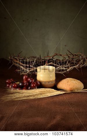 Table with cup of wine, bread, grapes, wheat, and crown of thorns