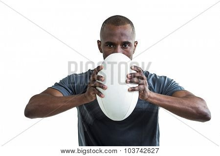 Portrait of sportsman pressing rugby ball while standing over white background
