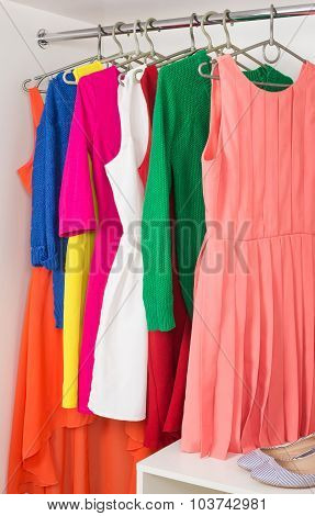 row of bright colorful dress hanging on coat hanger