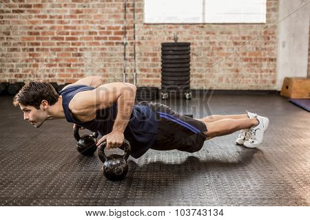 Man doing push ups with kettlebell at the gym