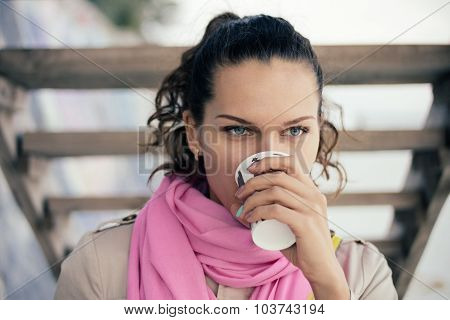 Woman In A Beige Jacket And A Pink Scarf Drinking Coffee From A Paper Cup Outdoors