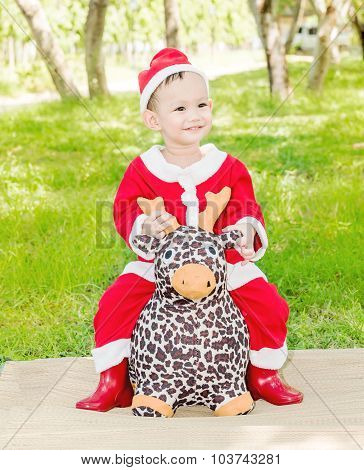 Asian Baby Boy In Santa Claus Suit Is Ridding