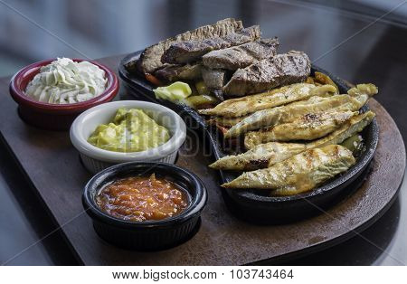 Mexican steak and chicken fajitas in iron plate