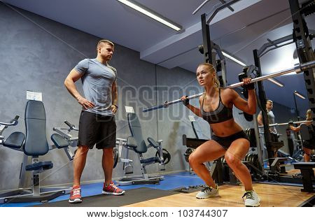sport, fitness, bodybuilding, lifestyle and people concept - man and woman with bar flexing muscles in gym