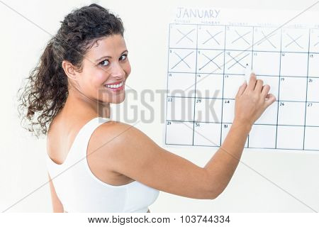 Portrait of happy pregnant woman marking off dates on calendar against white background