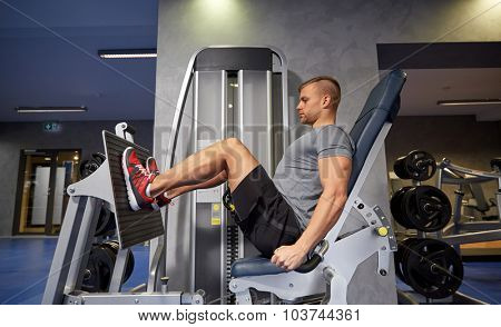 sport, fitness, bodybuilding, lifestyle and people concept - man exercising and flexing leg muscles on gym machine